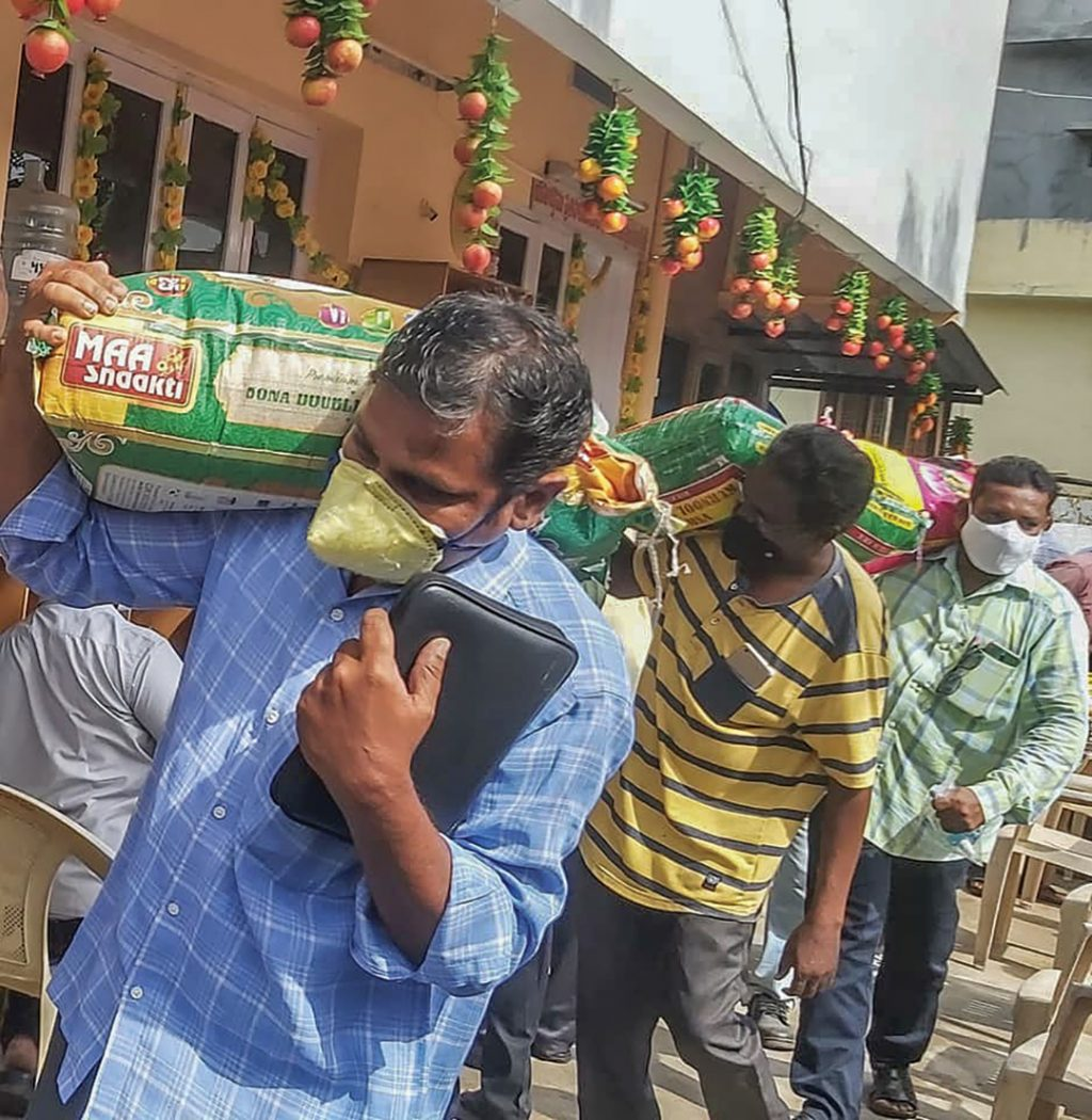 With a Bible in one hand and a bag of rice in the other, a minister in India heads home during a deadly wave of the COVID-19 delta variant.
