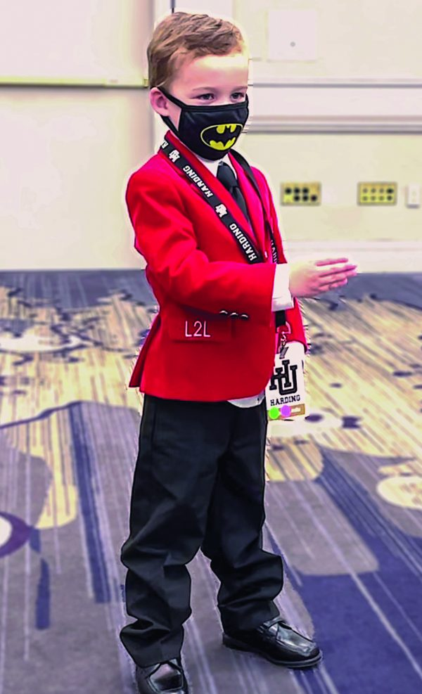 Three-year-old Joshua Johnson of the Deerfoot Church of Christ in Birmingham, Ala., leads a song earlier this year at the Lads to Leaders convention in Little Rock, Ark. His red blazer was a gift from Lads to Leaders founder Jack Zorn, his late wife, Frances, and their daughter, Rhonda Zorn Fernandez, lifelong friends of Joshua's parents. COVID-19 canceled the 2020 Lads to Leaders and Leadership Training for Christ conventions, which draw thousands of participants from Churches of Christ. This year some churches hosted mini-conventions at their buildings. A few of the larger conventions resumed with reduced attendance, social distancing and the occasional superhero mask.