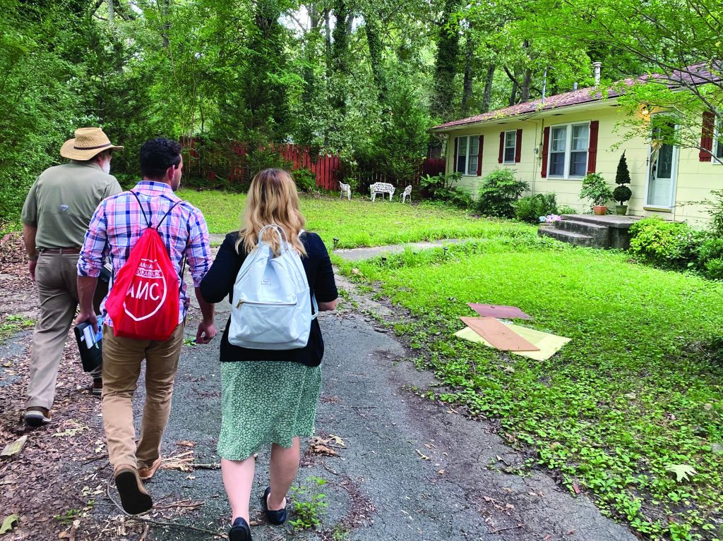 Ted Okolichany, Micah Trujillo and his mother, Julie Trujillo, approach a home during the American Mission Campain in Rome, Ga.