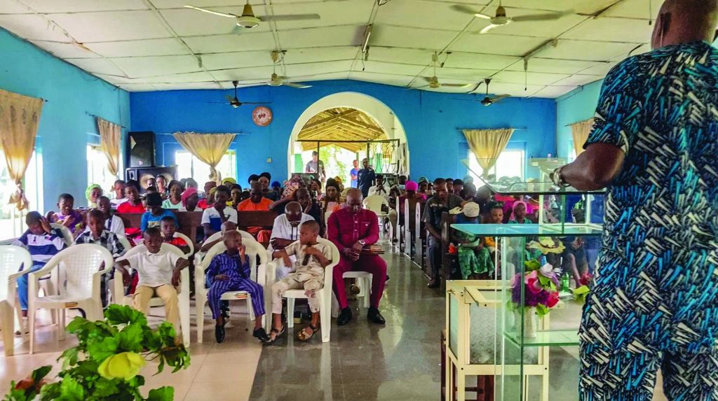 A Church of Christ worships in southeastern Nigeria while an armed guard stands at the back of the auditorium.
