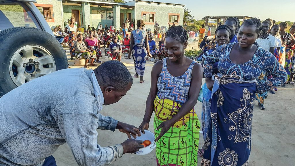 Expectant mothers line up to receive fruits and vegetables from Rodgers Namuswa at the Kalomo Hospital Mother's Shelter in Zambia.