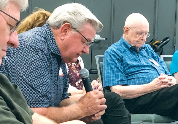Budo Perry, an engineer who did mission work in Brazil in the late 1960s, prays during a time of fellowship among family and friends of the São Paulo team.