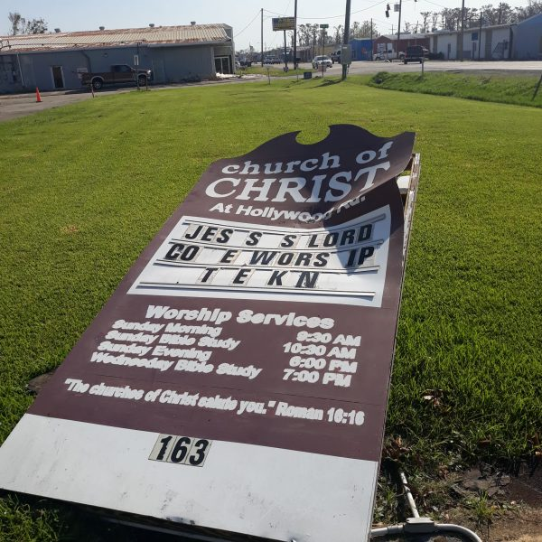 The Hollywood Road Church of Christ sign lies on the ground damaged after the storm.