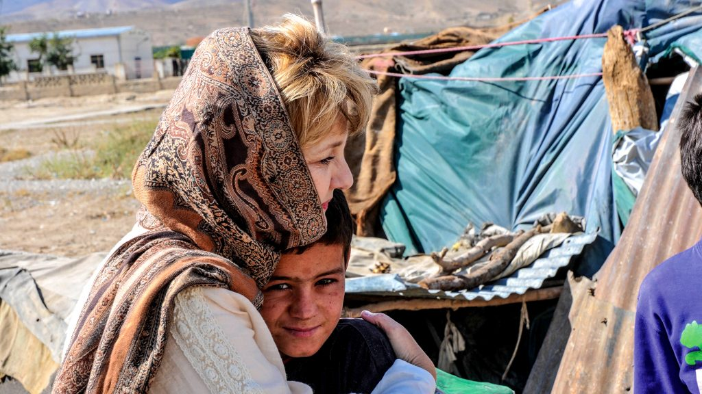 In an Afghanistan refugee camp, Jan Bradley hugs a boy who had lost both of his arms. Thousands of Afghan children have been killed or seriously injured during decades of conflict.