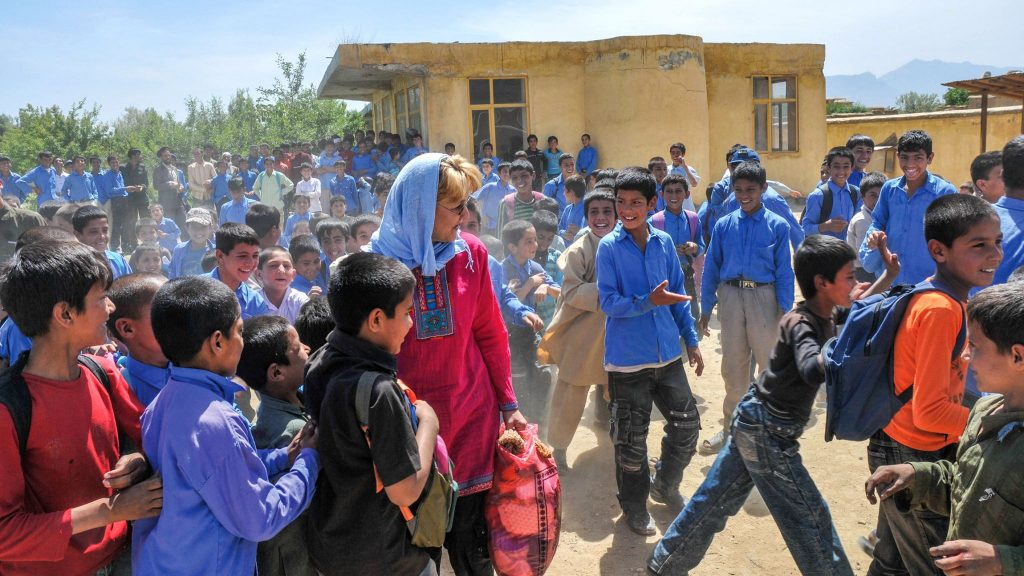 Jan Bradley meets students at a school in Afghanistan's Parwan Province, where she and her husband handed out school supplies. and soccer balls.
