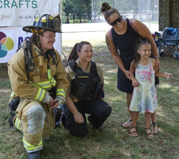 First responders pose for a photo with a child at Carolina Bible Camp's bluegrass festival Sept. 11.