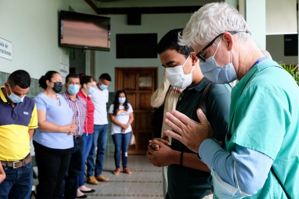 Dr. Chad Eustis, far right, prays in English with patients while Carlos Ponce, right, translates the prayer into Spanish at the Good Samaritan Medical Center owned by Predisan Health Ministries.