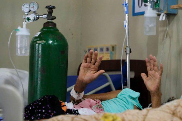 A patient raises her hands in prayer during a visit from Carlos Rivera, one of the rotating chaplains.