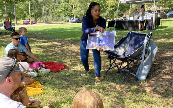 """Talitha Vickers reads her book, """"Why My Hero Had To Go,"""" to children at the Carolina Bible Camp Bluegrass Festival."""
