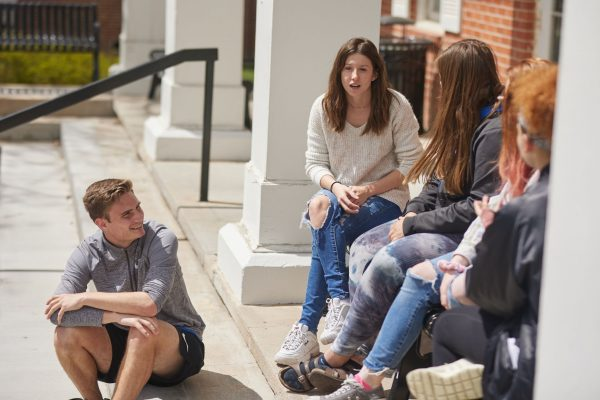 York College students sit and talk on the steps of a building on the university's campus.