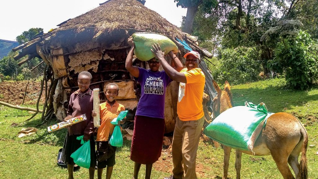 David Marangach of Christian Relief Fund delivers food to a sponsored child and his family by donkey in a rural communuty near Mount Elgon in Kenya.