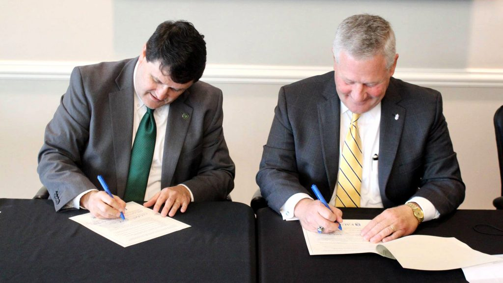 HCU President W. Kirk Brothers, left, and Faulkner University President Mike Williams, right, sign a memorandum of agreement between the two schools on Sept. 30.