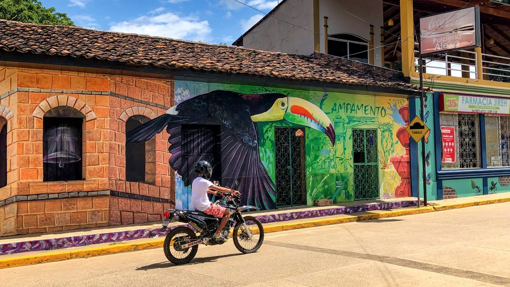 A motorbike speeds by one of the murals near the Campamento town square.