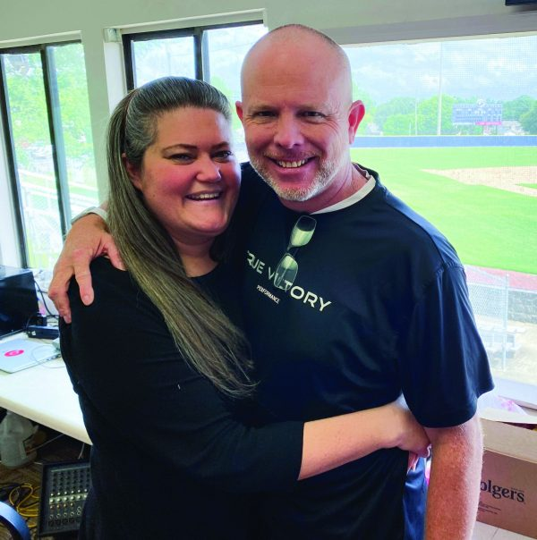 Patrick McCarthy and his wife, Katie Beth, share a hug in the press box overlooking the baseball field at Faulkner University in Montgomery, Ala.